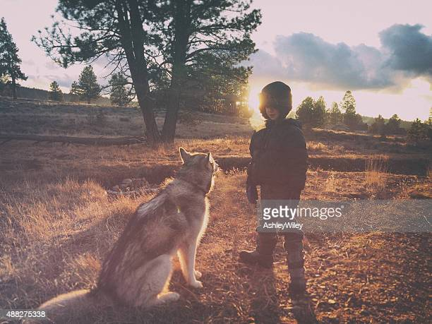 Boy and dog in the wilderness in autumn