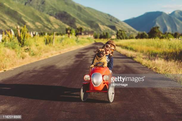 niño y perro en toy racing car - animal win fotografías e imágenes de stock