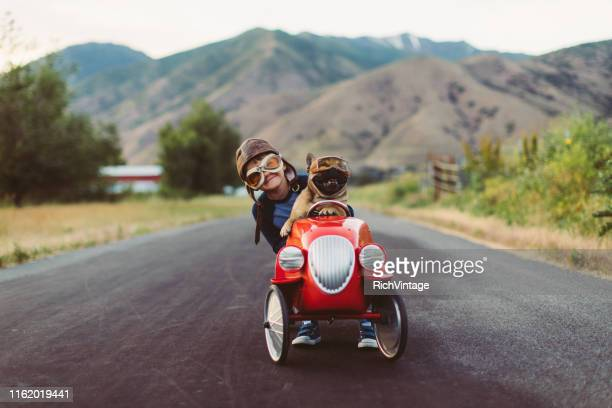 boy and dog in toy racing car - flying goggles stock pictures, royalty-free photos & images