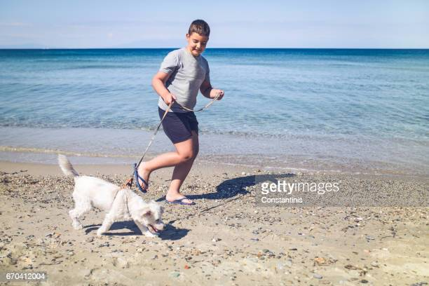 Boy and dog running along a sandy beach on a summer day