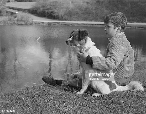 boy and dog sitting near river - {{relatedsearchurl(carousel.phrase)}} stock pictures, royalty-free photos & images