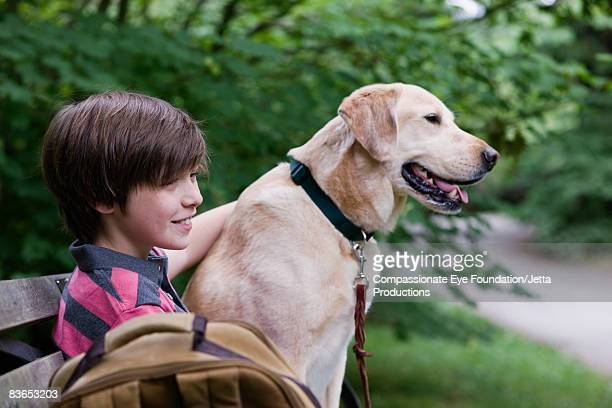 Boy and dog sitting on bench