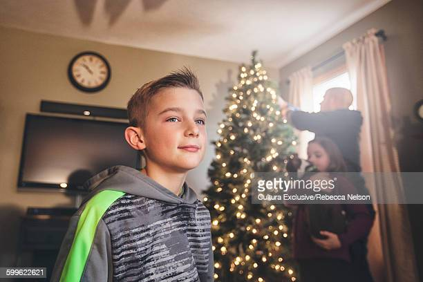 Boy and family decorating Christmas tree, looking away smiling