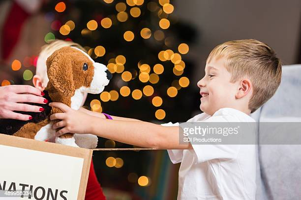 Boy and family donating used toys and clothing before Christmas