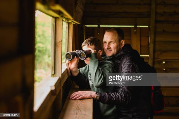 Boy and father birdwatching with binoculars