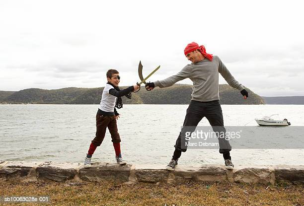 Boy (10-11) and father dressed as pirates, mock-duelling, on wall at edge of lake, side view