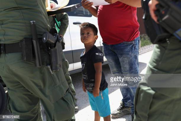 A boy and father from Honduras are taken into custody by US Border Patrol agents near the USMexico Border on June 12 2018 near Mission Texas The...