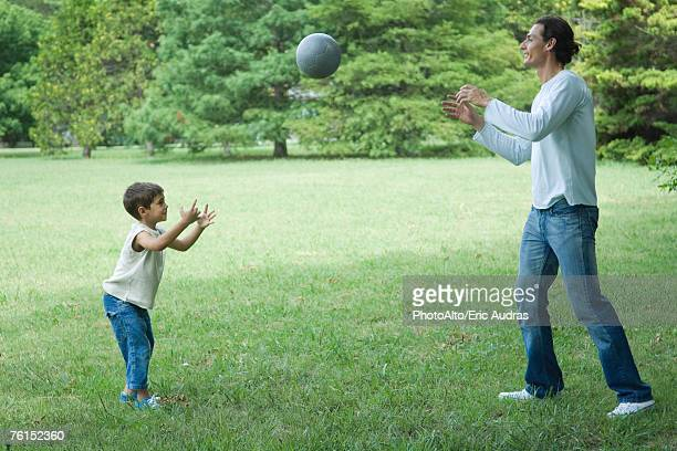 'Boy and father outdoors, throwing ball back and forth on a grassy lawn'