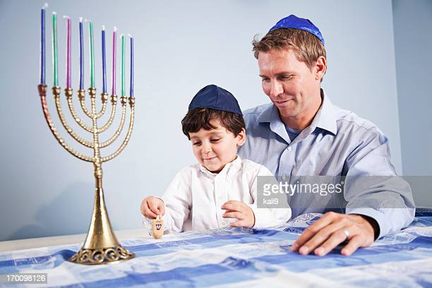 boy and father playing with dreidl - dreidel stock photos and pictures