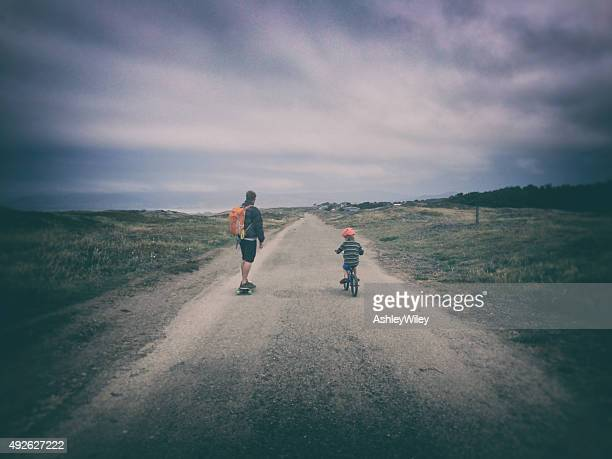 Boy and father riding down a dirt path on bike