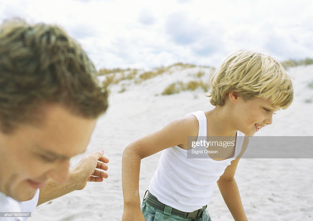 Boy and father running on beach : Stock Photo