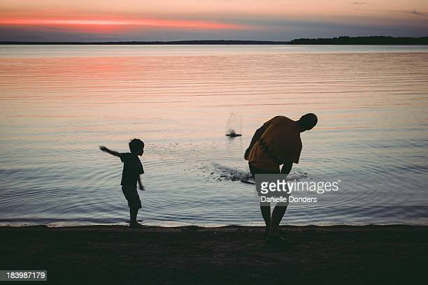 Boy and father skipping rocks at sunset
