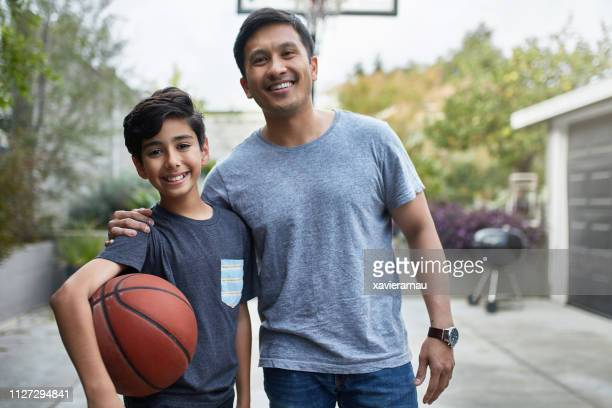 boy and father standing at basketball court - tee sports equipment stock pictures, royalty-free photos & images