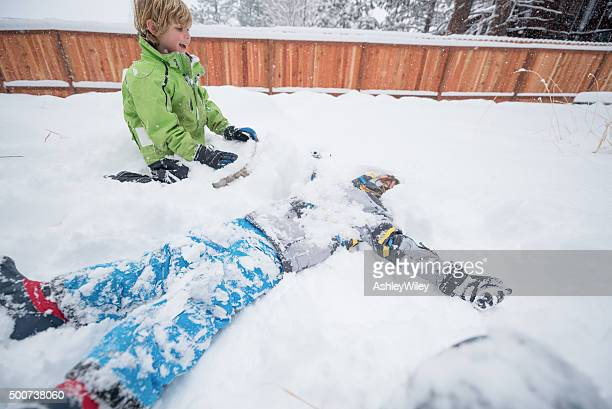 Boy and friend playing in snow in the backyard