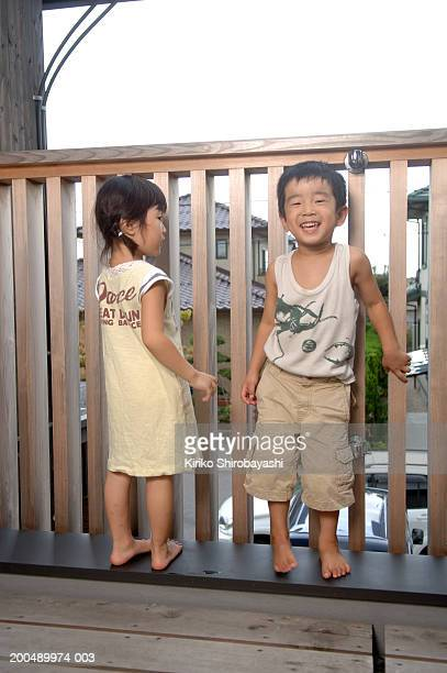 boy and girl 3-6) playing on verandah - yonago stock photos and pictures