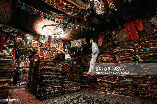 boy and girl among oriental carpets - anatolia stock pictures, royalty-free photos & images