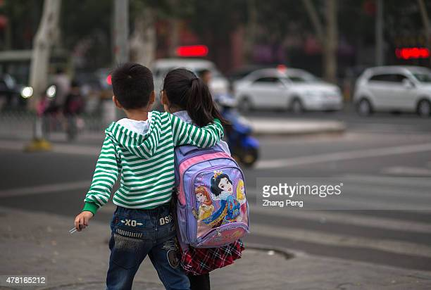 A boy and girl are going home together after school In China trafficking of children Stayathome children and Children abuse are the biggest social...
