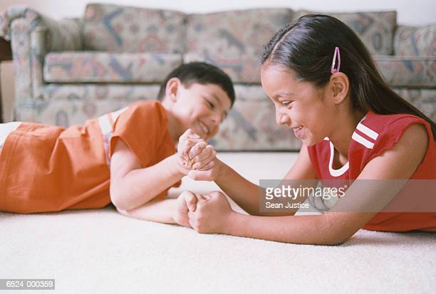 boy and girl arm wrestling - girl wrestling stock pictures, royalty-free photos & images