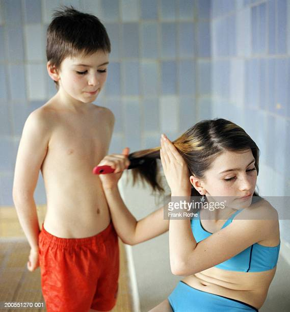 Boy and girl (10-11) at pool changing room, girl combing hair