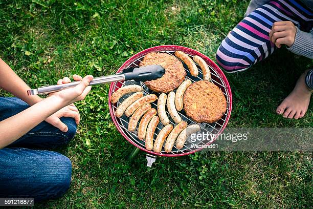 Boy and girl barbecuing sausages and meat n garden