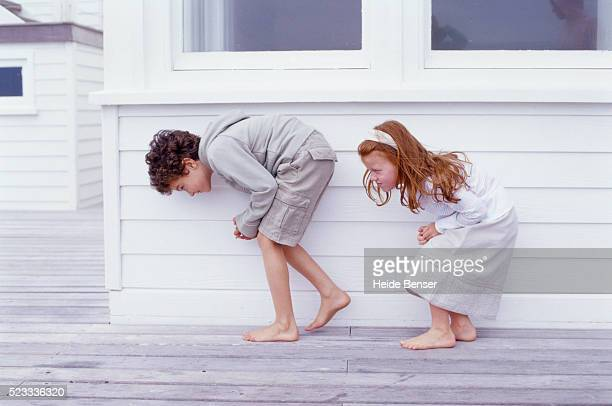 Boy and Girl Bending Under Window