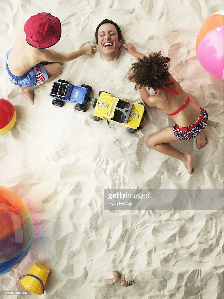 Boy and girl (5-7) beside father buried in sand, overhead view : Stock Photo