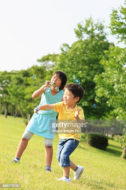 Boy and Girl Blowing Soap Bubbles