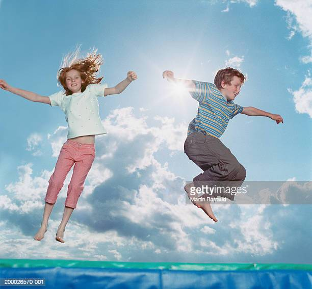 Boy and Girl (8-11) bouncing on trampoline