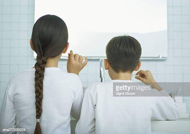 Boy and girl brushing teeth, rear view