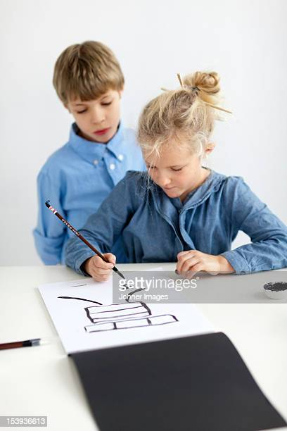 Boy and girl caligraphing chinese signs