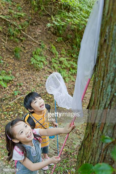 Boy and Girl Catching Insects