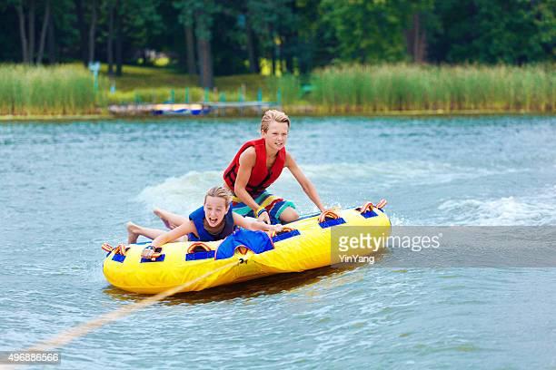Boy and Girl Children Tubing on Minnesota Lake in Summer