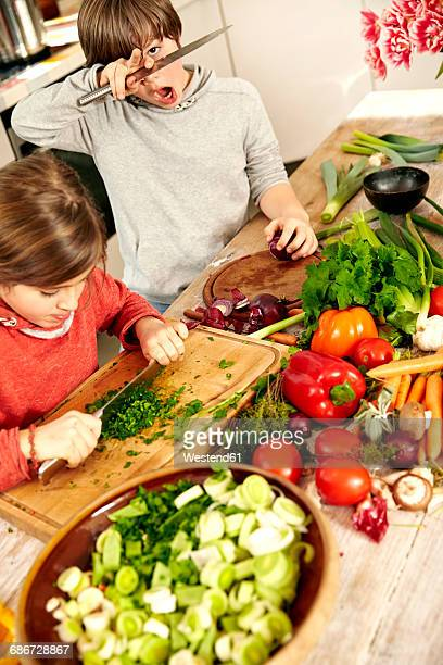 Boy and girl chopping vegetables in the kitchen