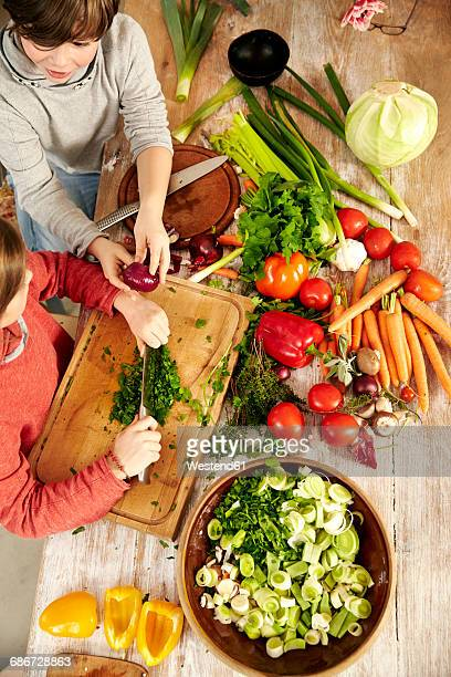 Boy and girl chopping vegetables in the kitchen, top view