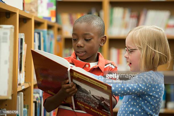 boy and girl classmates sharing book in library - history stock pictures, royalty-free photos & images