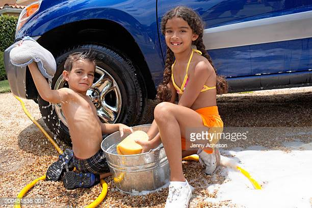 Boy and girl (6-8) cleaning car, crouching by water bucket, portrait