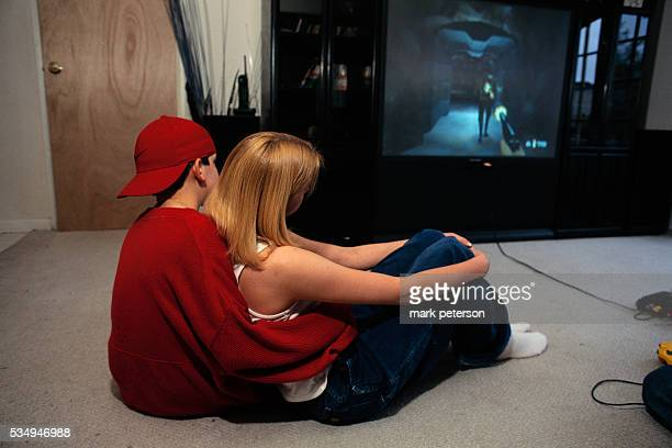 Boy and Girl Cuddling in Front of Television