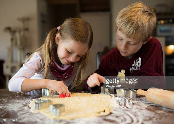 Boy and girl cutting out cookies with cookie cutter