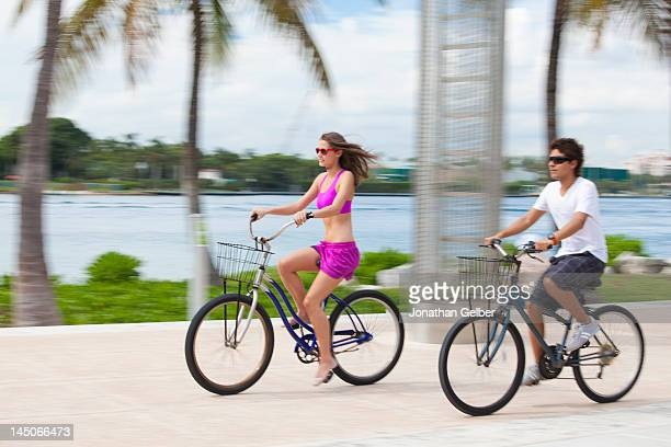 Boy and girl cycling on promenade