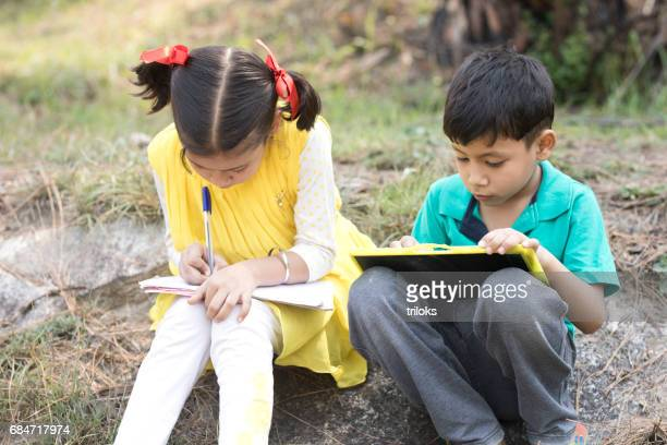 Boy and girl doing homework outdoors