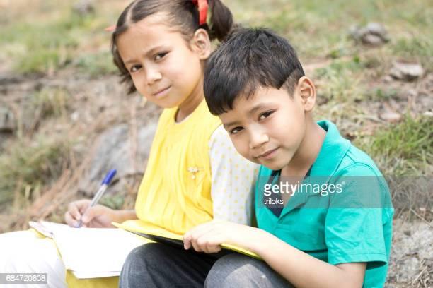 Boy and girl doing homework outdoors