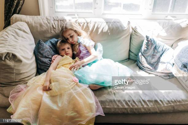 a boy and girl dressed in princess dresses sit on a couch. - princess stock pictures, royalty-free photos & images