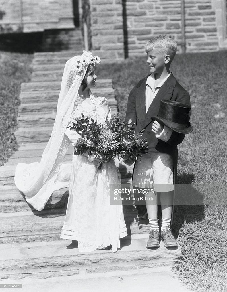 Boy and girl dressed up as bride and groom, outdoors on steps. : Foto de stock