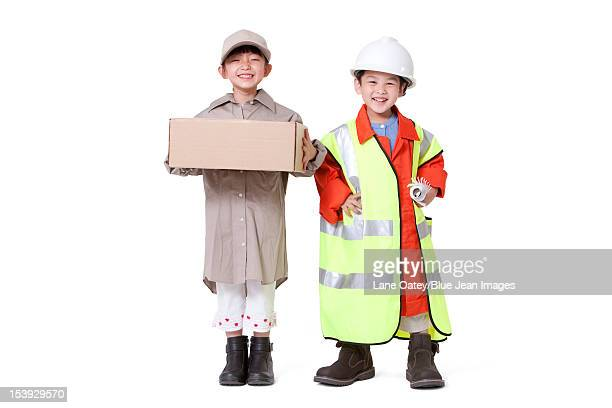 boy and girl dressing up like delivery person and engineer - kids costume engineer stock photos and pictures