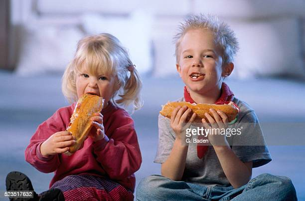 boy and girl eating baguettes - submarine sandwich stock pictures, royalty-free photos & images