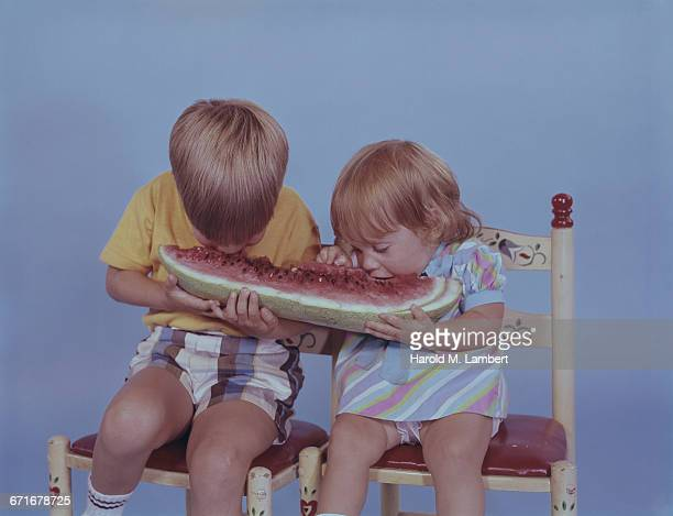 """boy and girl eating watermelon, studio shot "" - {{relatedsearchurl(carousel.phrase)}} imagens e fotografias de stock"