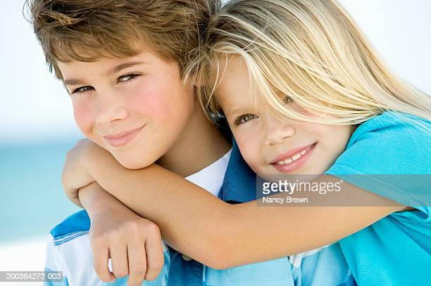 Boy and girl (7-9) embracing  portrait, close-up
