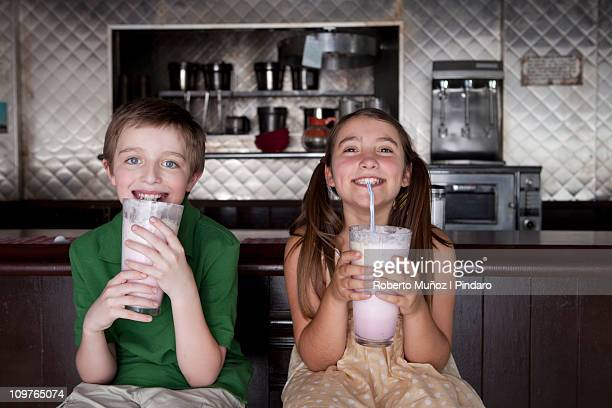 boy and girl enjoying milkshakes - milkshake imagens e fotografias de stock