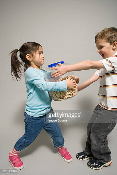 A boy and girl fighting over a jar of biscuits