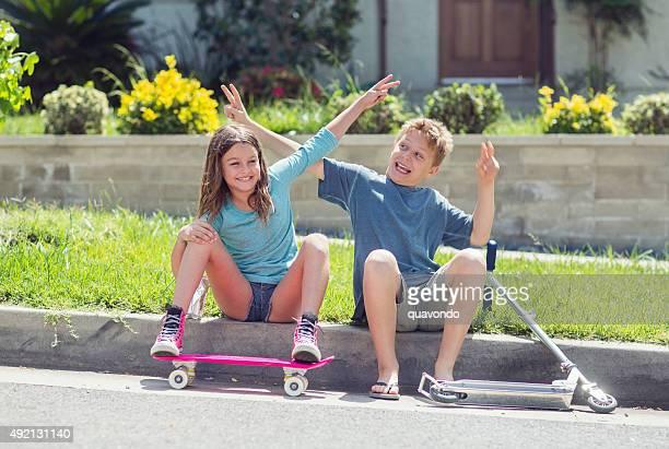 Jungen und Mädchen Flirten auf Gehweg mit skateboard und scooter